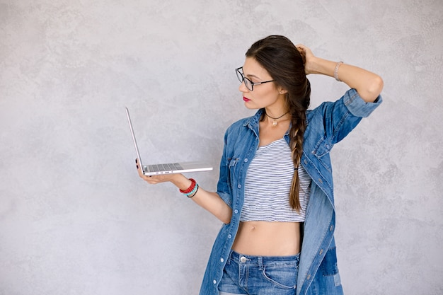 Mulher com laptop toca o cabelo com a mão