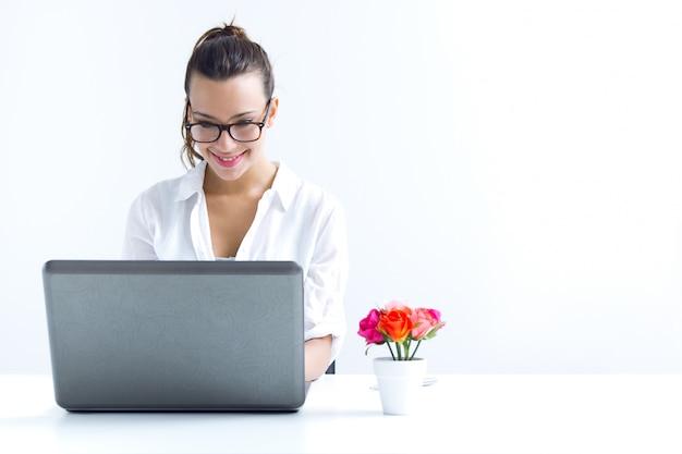 Mulher com laptop trabalhando em casa