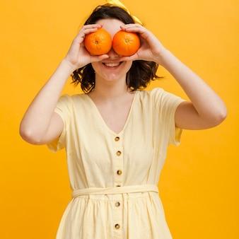 Mulher com laranjas como binóculo