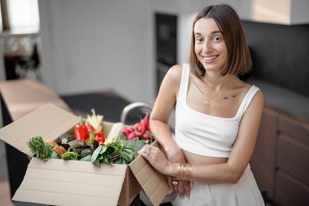 Mulher com legumes frescos embalados em caixa de papelão na cozinha