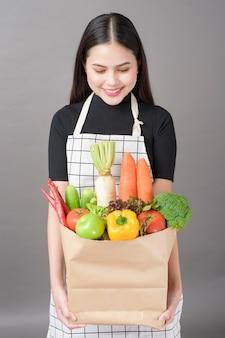Mulher com legumes na sacola de compras
