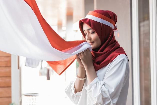 Mulher com lenço beijando a bandeira da indonésia
