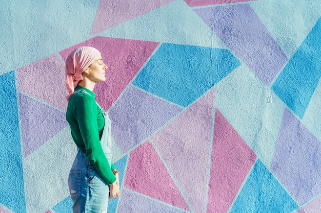 Mulher com lenço na cabeça, combate ao câncer em uma parede colorida