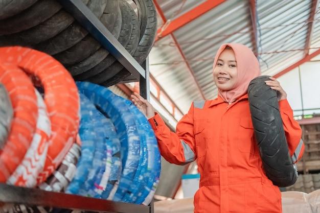 Mulher com lenço na cabeça e uniforme do wearpack em pé ao lado do suporte de pneus ao carregar um pneu de motocicleta em uma oficina mecânica