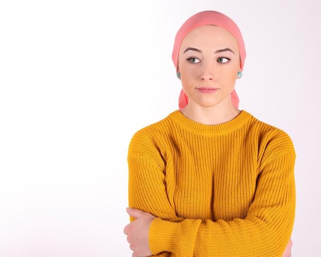 Mulher com lenço rosa com câncer, preocupada com os braços cruzados