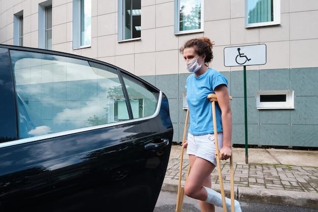 Mulher com lesão na perna entra no carro gesso ortopédico muletas ortopédicas