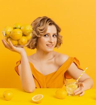Mulher com limonada e segurando a tigela s com limões