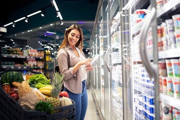 Mulher com lista de compras em pé ao lado da geladeira no supermercado e verificando o carrinho