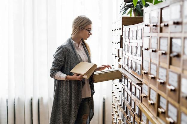 Mulher com livro à procura de cartão no catálogo