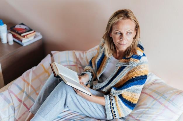 Mulher com livro em quarentena em casa