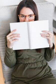 Mulher com livro sentado na cadeira