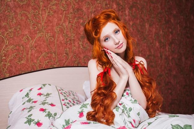 Mulher com longos cabelos cacheados vermelhos reunidos em tranças na camisola na cama debaixo de um cobertor. garota ruiva com um rosto bonito, pele pálida, olhos azuis e aparência incomum e brilhante no quarto