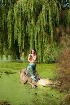 Mulher com longos cabelos castanhos e vestida como uma sereia senta-se na pedra sobre a água