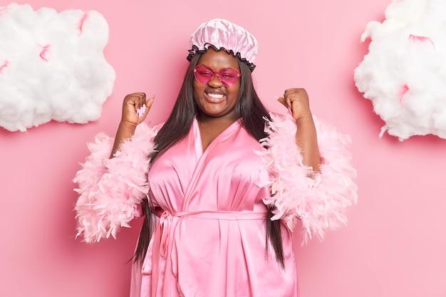 Mulher com longos cabelos escuros sente-se com sorte depois de atingir o objetivo cerrar os punhos usando um chapéu à prova d 'água, roupão, poses internas em rosa