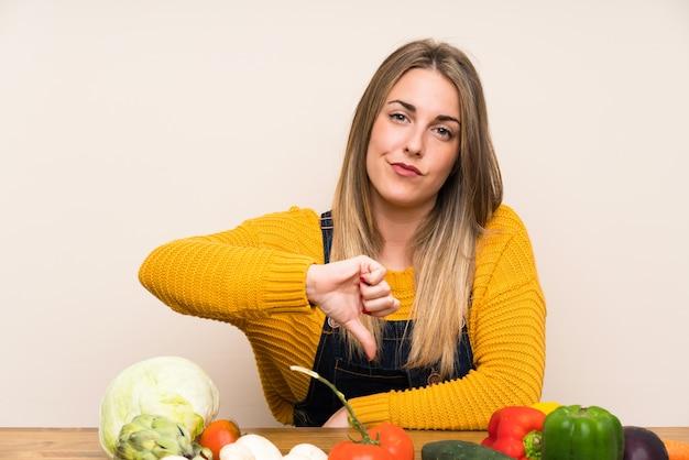 Mulher, com, lotes, de, legumes, mostrando, polegar baixo, sinal