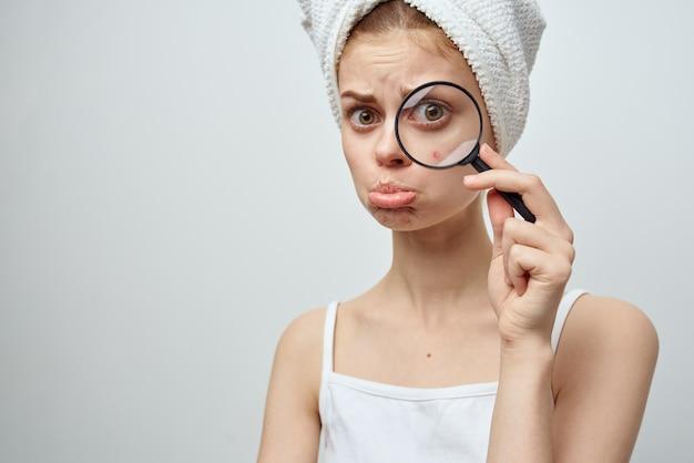 Mulher com lupa na mão e acne no rosto com uma toalha na cabeça