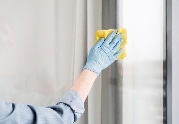 Mulher com luva de borracha, limpando a janela