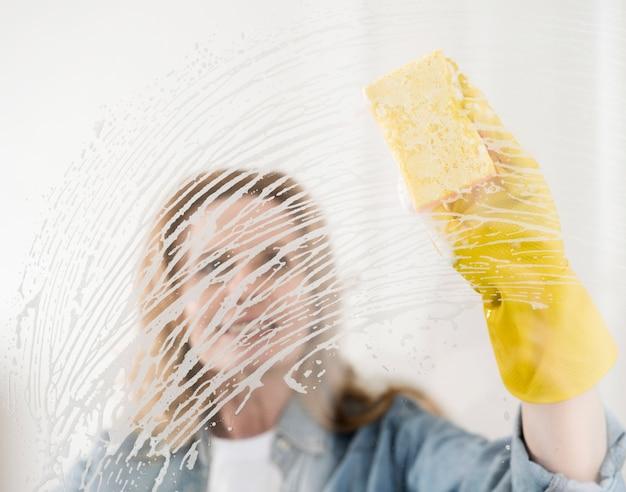 Mulher com luva de borracha, limpeza de janela com esponja