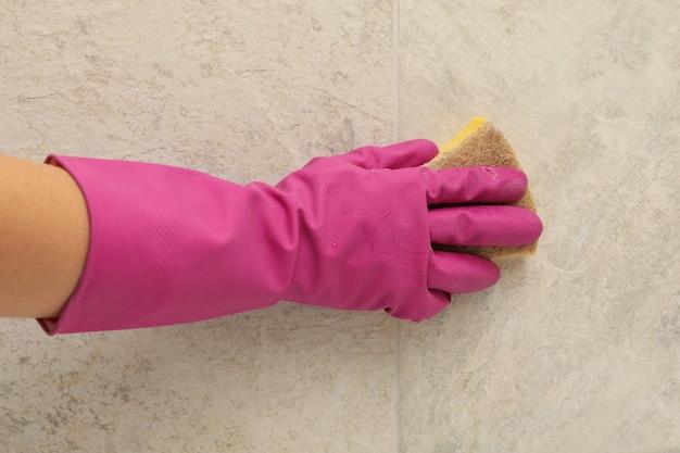 Mulher com luva de borracha rosa limpa azulejos