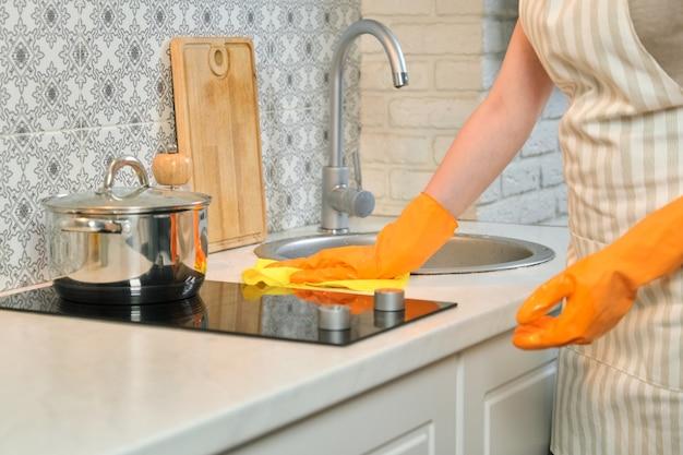 Mulher com luvas de avental limpando a cozinha depois de cozinhar, mãos femininas lavando fogão