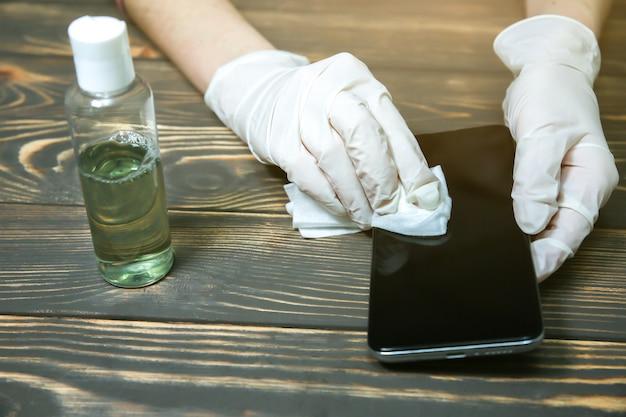 Mulher com luvas de borracha está desinfetando o smartphone com almofadas de algodão. anti-séptico durante a pandemia de coronavírus. perigo de vírus. dispositivos perigosos sujos. medidas de segurança.