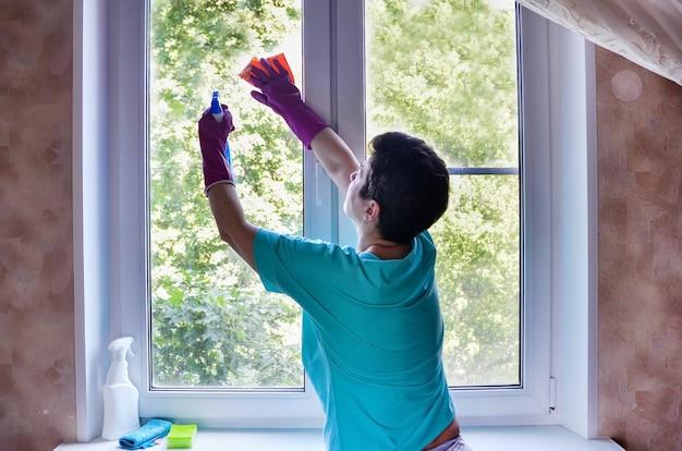Mulher com luvas de borracha lava a janela, segurando o spray para limpeza de janelas nas mãos. serviço de limpeza