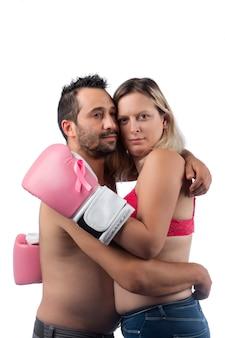 Mulher com luvas de boxe rosa abraçando o marido em apoio, simbolizando a conscientização do combate ao câncer de mama