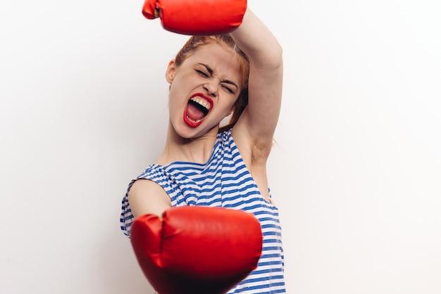 Mulher com luvas de boxe vermelhas em um penteado de maquiagem com fundo claro de camiseta listrada