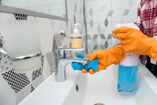 Mulher com luvas de proteção segurando um spray e um pano enquanto limpa a casa.