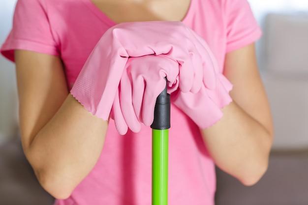 Mulher com luvas de proteção usando um esfregão para limpar o chão