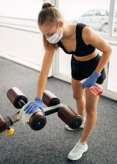 Mulher com luvas e máscara médica no ginásio desinfetando equipamentos
