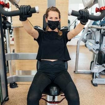 Mulher com luvas e máscara médica treinando na academia usando equipamentos