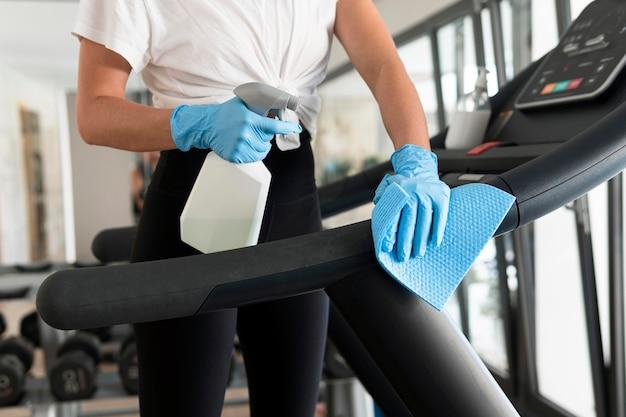 Mulher com luvas e solução de limpeza, desinfetando equipamentos de ginástica