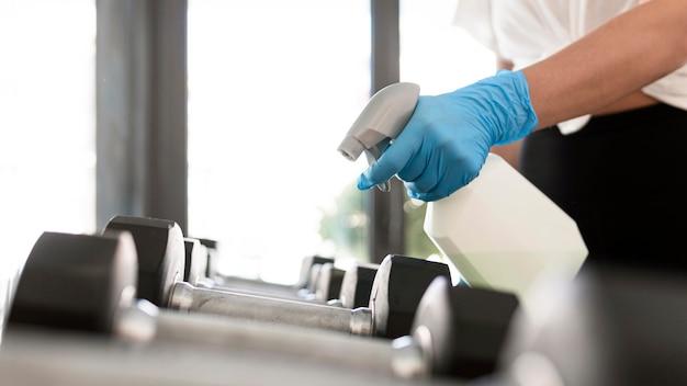 Mulher com luvas e solução de limpeza desinfetando pesos de academia