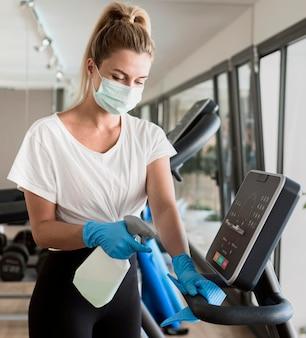 Mulher com luvas limpando equipamento de ginástica enquanto usa máscara médica