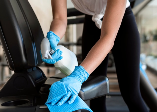 Mulher com luvas limpando equipamentos de ginástica