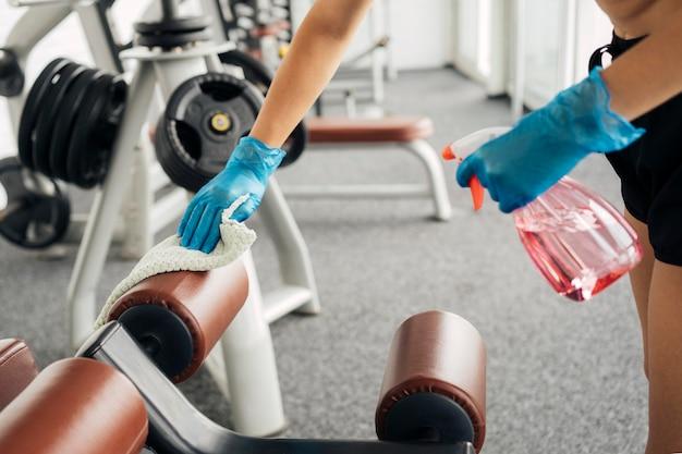 Mulher com luvas na academia desinfetando equipamentos