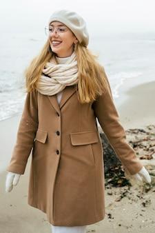 Mulher com luvas na praia durante o inverno