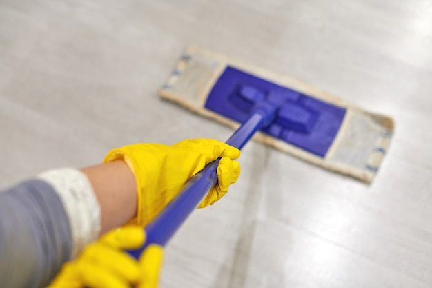 Mulher com luvas protetoras de borracha amarela usando esfregão úmido enquanto limpa a sala