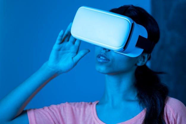 Mulher com luz azul usando fone de ouvido de realidade virtual