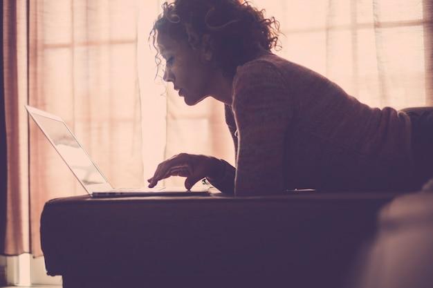 Mulher com luz de fundo da janela e calça jeans deitada no sofá trabalhando com o computador laptop em completo relaxamento