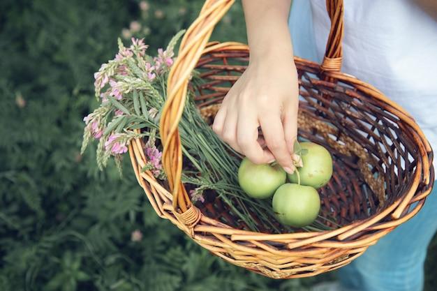 Mulher com maçã na cesta no jardim