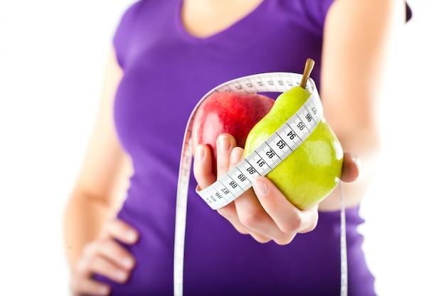 Mulher com maçã, pêra e fita métrica