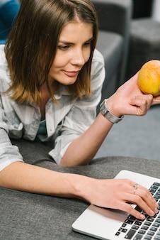 Mulher, com, maçã, usando computador portátil, ligado, sofá