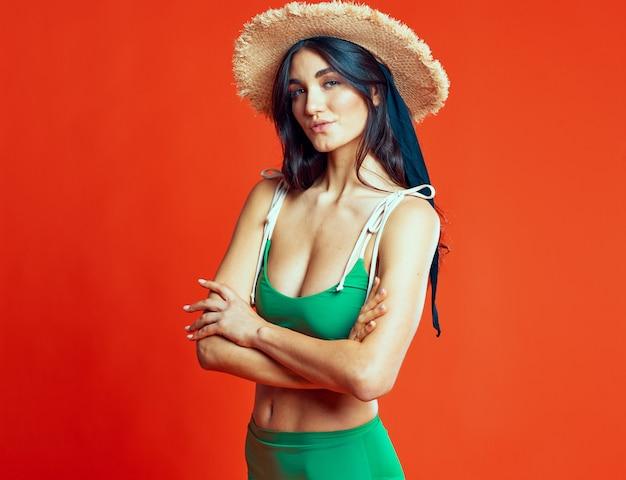Mulher com maiô verde chapéu de praia férias de verão fundo vermelho