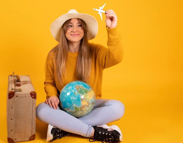 Mulher com mala e chapéu olha para o globo da terra quer viajar