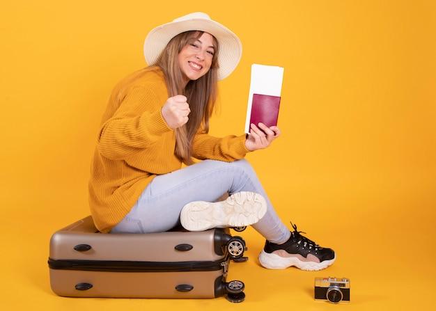Mulher com mala e chapéu passaporte, espaço amarelo