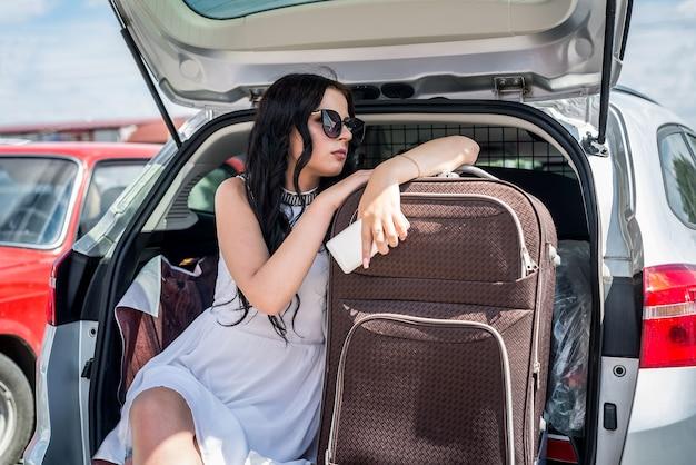 Mulher com mala e telefone sentada no porta-malas do carro