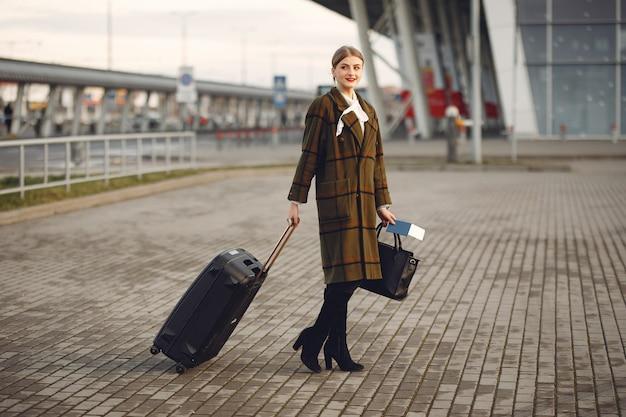 Mulher com mala em pé no aeroporto