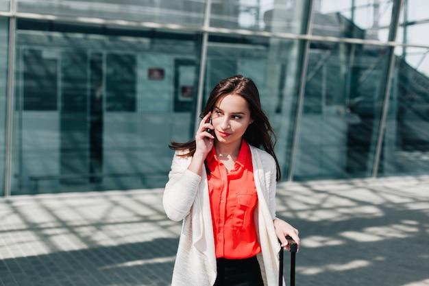 Mulher com mala vermelha anda ao longo do aeroporto e fala no telefone